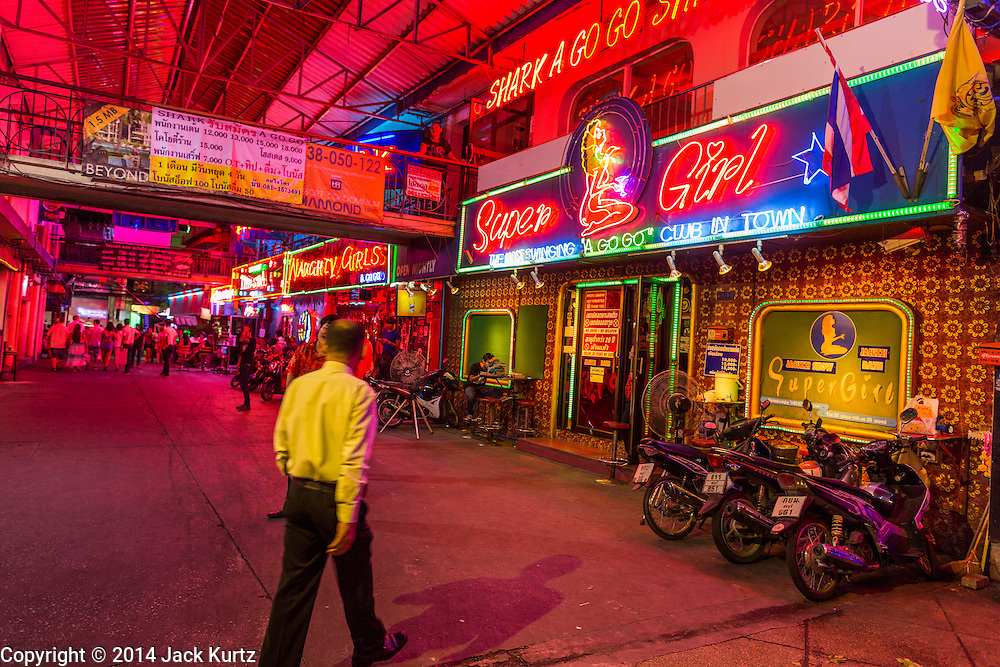 "26 SEPTEMBER 2014 - PATTAYA, CHONBURI, THAILAND: A man walks into a go-go bar near Walking Street in Pataya. Pataya, a beach resort about two hours from Bangkok, has wrestled with a reputation of having a high crime rate and being a haven for sex tourism. After the coup in May, the military government cracked down on other Thai beach resorts, notably Phuket and Hua Hin, putting military officers in charge of law enforcement and cleaning up unlicensed businesses that encroached on beaches. Pattaya city officials have launched their own crackdown and clean up in order to prevent a military crackdown. City officials have vowed to remake Pattaya as a ""family friendly"" destination. City police and tourist police now patrol ""Walking Street,"" Pattaya's notorious red light district, and officials are cracking down on unlicensed businesses on the beach.     PHOTO BY JACK KURTZ"