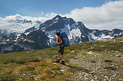 Adult male backpacker hiking on Red Face Mountain, Challenger and Whatom Peaks are in the bckground, North Cascades National Park