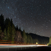 Light trails from passing 18-wheelers are eclipsed by towering Douglas fir trees as stars swirl around Polaris, the North Star. Shasta County, CA. Mt. Shasta can just be made out in the corner of the image.