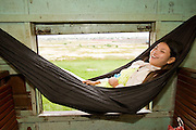 01 JULY 2006 - PHNOM PENH, CAMBODIA: A girl in a hammock on the Phnom Penh - Battambang passenger train. While much of Cambodia's infrastructure has been rebuilt since the wars which tore the country apart in the late 1980s, the train system is still in disrepair. There is now only one passenger train in the country. It runs from Phnom Penh to the provincial capitol Battambang and it runs only one day a week. It takes 12 hours to complete the 190 mile journey.  Photo by Jack Kurtz / ZUMA Press