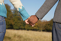Couple standing in field holding hands mid section back view
