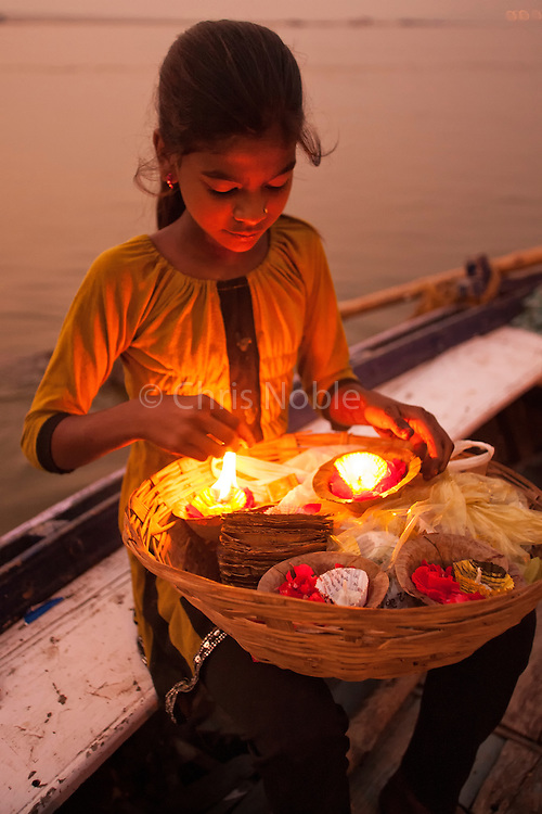 A young girl sells floating candles to be used as a blessing from a boat on the Ganges River in Varanasi India.