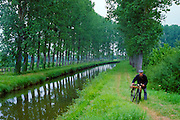 A man walking beside a canal with his bicycle in France