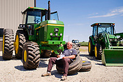 "06 AUGUST 2020 - FAIRFIELD, IOWA: RANDY STEWART, from Salem, IA, sits on the tires of a John Deere tractor during the auction on the Adam Farm near Fairfield. Gary Adam, 72 years old, has been farming in the Fairfield area since 1971. He decided to retire this year because he wants to travel and because it's so difficult to make money in farming this year. He said he wants to ""shed the risk and responsibility. If things were super good, like they were 2006-2012, I might stay in it, but they're not."" An increasing number of farmers in the Midwest are retiring this year as it becomes harder to make money on crops. In addition to low prices, Iowa farmers are being hit with a drought this year, with well below average rain over most of the state. Because of the COVID-19 pandemic, the auction on Adam's farm was one of the first live in person auctions since winter. Most auctions are now done on line.     PHOTO BY JACK KURTZ"