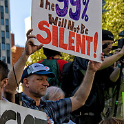 Man holding up sign &quot;The 99% Will Not Be Silent!&quot;<br /> <br /> Grassroots, nonviolent efforts of the  Occupy Wall Street movement , the 99% protesters in Foley Square in lower Manhattan before they march to  Zuccotti Park. <br /> <br /> This movements is about income equality and social justice issues.
