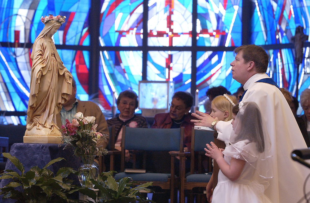 MAY CROWNING -- Camillian Fr. Albie Schempp kneels before a statue of Mary along with two young girls during a May crowning ceremony at the chapel inside San Camillo Retirement Community in Wauwatosa, Wis. (Photo by Sam Lucero)