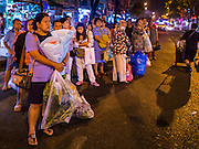 29 FEBRUARY 2016 - BANGKOK, THAILAND:  People wait for a city bus in front of the Bangkok flower market. Many of the sidewalk vendors around Pak Khlong Talat, the Bangkok flower market, closed their stalls Monday. As a part of the military government sponsored initiative to clean up Bangkok, city officials announced new rules for the sidewalk vendors that shortened their hours and changed the regulations they worked under. Some vendors said the new rules were confusing and too limiting and most vendors chose to close Monday rather than risk fines and penalties. Many hope to reopen when the situation is clarified.   PHOTO BY JACK KURTZ
