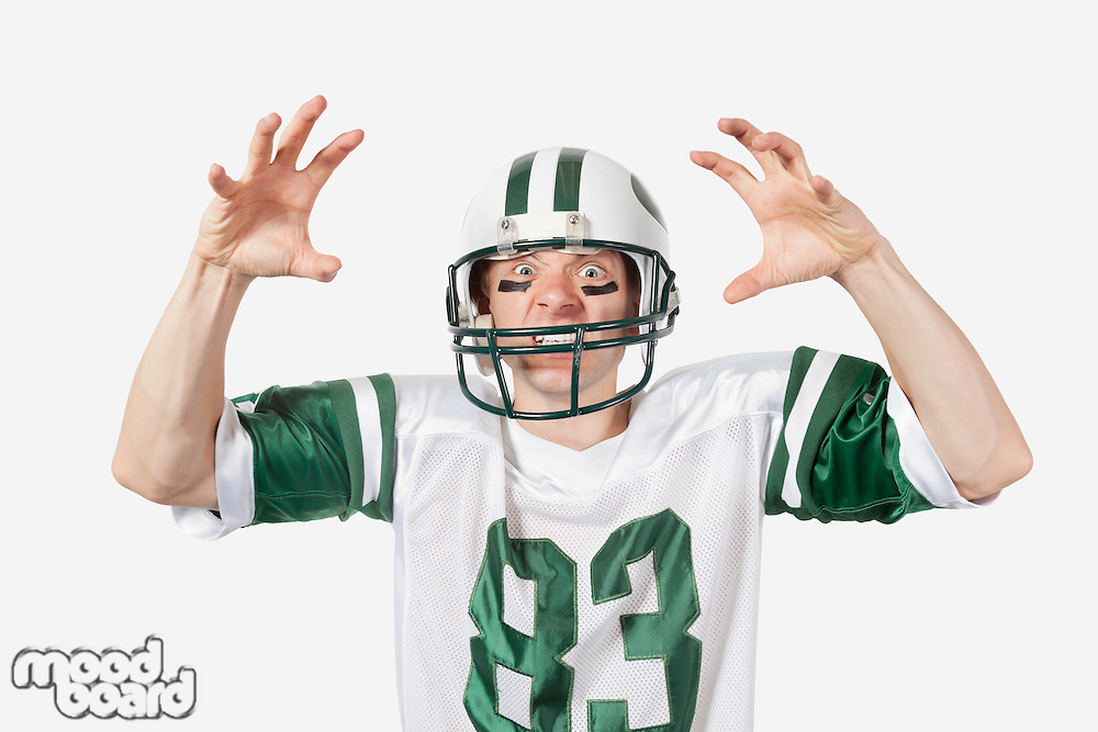 Portrait of angry young man in football uniform gesturing over gray background