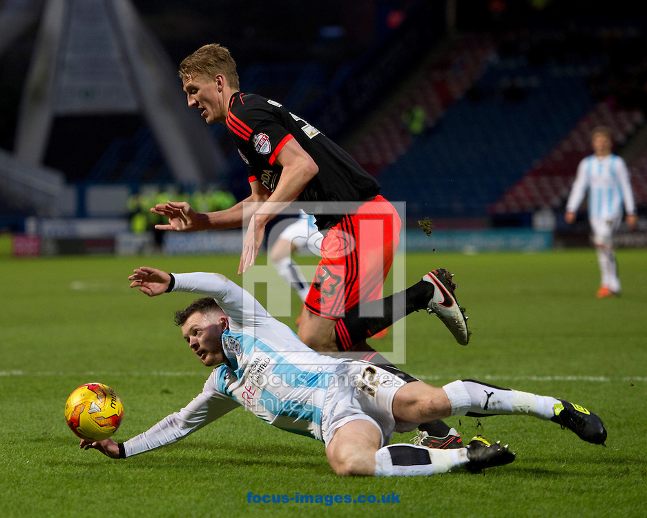 Harry Bunn of Huddersfield Town tumbles under a challenge by Dan Burn of Fulham during the Sky Bet Championship match at the John Smiths Stadium, Huddersfield<br /> Picture by Russell Hart/Focus Images Ltd 07791 688 420<br /> 16/01/2016