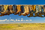 Old cowboy boots on posts on prarie at edge of sand dunes, Great Sand Hills, Saskatchewan, Canada