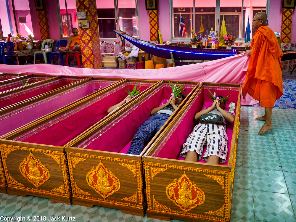 """14 FEBRUARY 2018 - BANG KRUAI, NONTHABURI, THAILAND: People in coffins participate in a resurrection ceremony at Wat Ta Khien, about 45 minutes from Bangkok in Nonthaburi province. The temple is famous for the """"floating market"""" on the canal that runs past the temple and for the """"resurrection ceremonies"""" conducted by monks at the temple. People lie in a coffin and ritualistically die before being reborn. Adherents believe it will improve their karma and help make up for past sins.         PHOTO BY JACK KURTZ"""