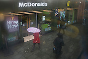 Aerial view through misted bus window of McDonalds restaurant and Londoners drab lives below during seasonal downpour of rain.