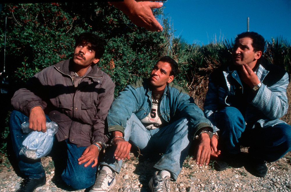 A Guardia Civil patrolman apprehends three illegal immigrants who entered Spain and the open borders of the European Union by crossing of the Strait of Gibraltar from Morocco..Tarifa, Spain. October 1996..Photo © J.B. Russell