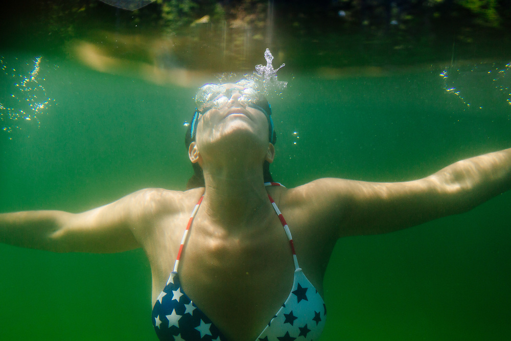 Young woman swimming under water in quarry.