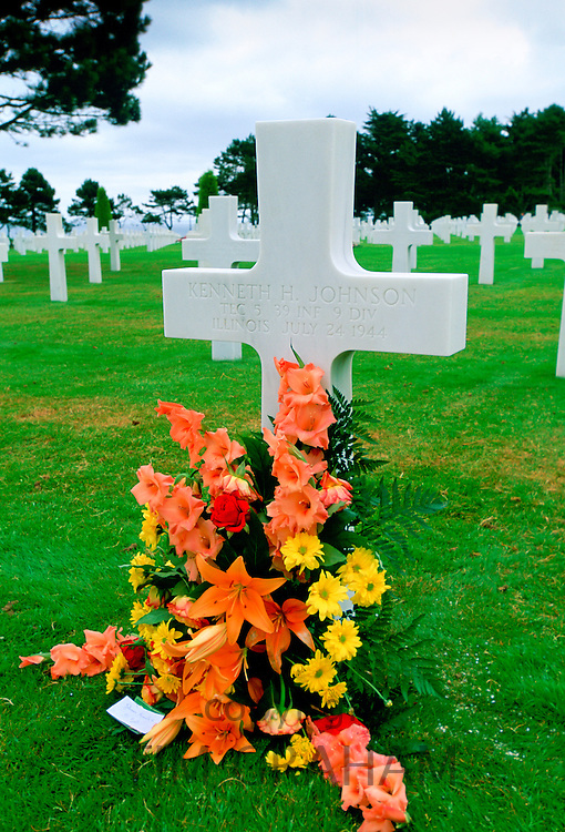 Headstones at a United States Military Cemetery at Utah Beach in Normandy, France.  Flowers have been left beside one of the crosses dedicated to a US serviceman.