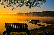 Bench and boat in fog at sunrise on Tilton Lake<br /> Sudbury<br /> Ontario<br /> Canada