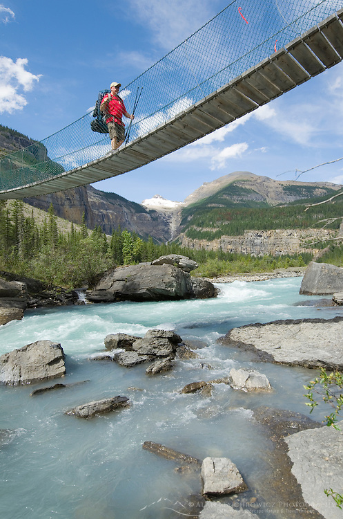 Hiker crossing suspension bridge on the Berg Lake Trail, Mount Robson Provincial Park British Columbia Canada