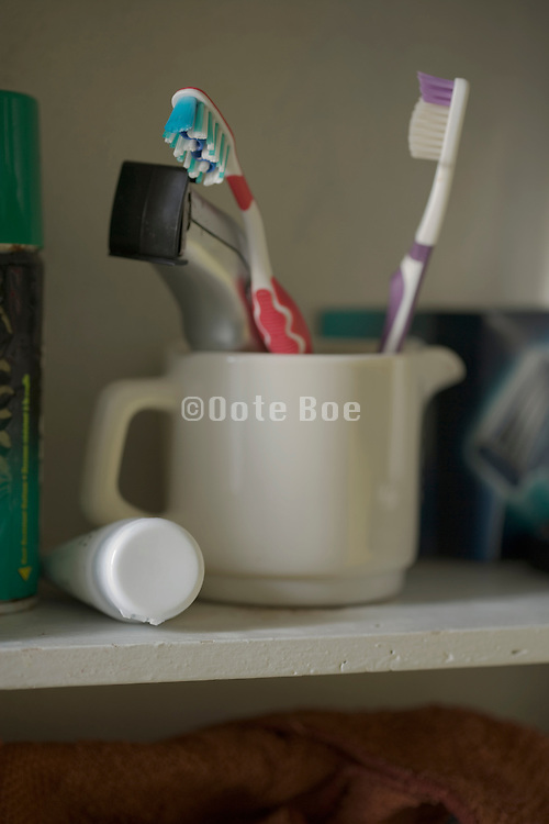 toothbrushes and electric shaver in a mug