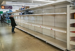 © Licensed to London News Pictures. 06/03/2020. Cobham, UK. As the threat of the coronavirus bug continues a shopper looks at empty toilet roll shelves in Sainsbury's in Cobham, Surrey. Photo credit: LNP