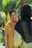 Two muslim woman in traditional clothing talking