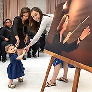 15-month old Riley pauses seeing a photo of her grandmother Nina Nash-Roberson during a dedication ceremony to name the choir hall after the long-time director of Central Michigan University choral activities and professor emeritus who died early this year.