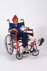 Portrait of young boy with leg in bandages using wheelchair,