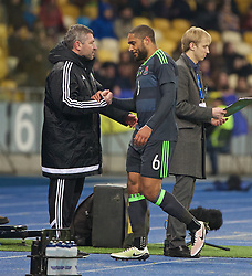 KIEV, UKRAINE - Easter Monday, March 28, 2016: Wales' captain Ashley Williams shakes hands with assistant manager Osian Roberts as he is substituted during the International Friendly match against Ukraine at the NSK Olimpiyskyi Stadium. (Pic by David Rawcliffe/Propaganda)