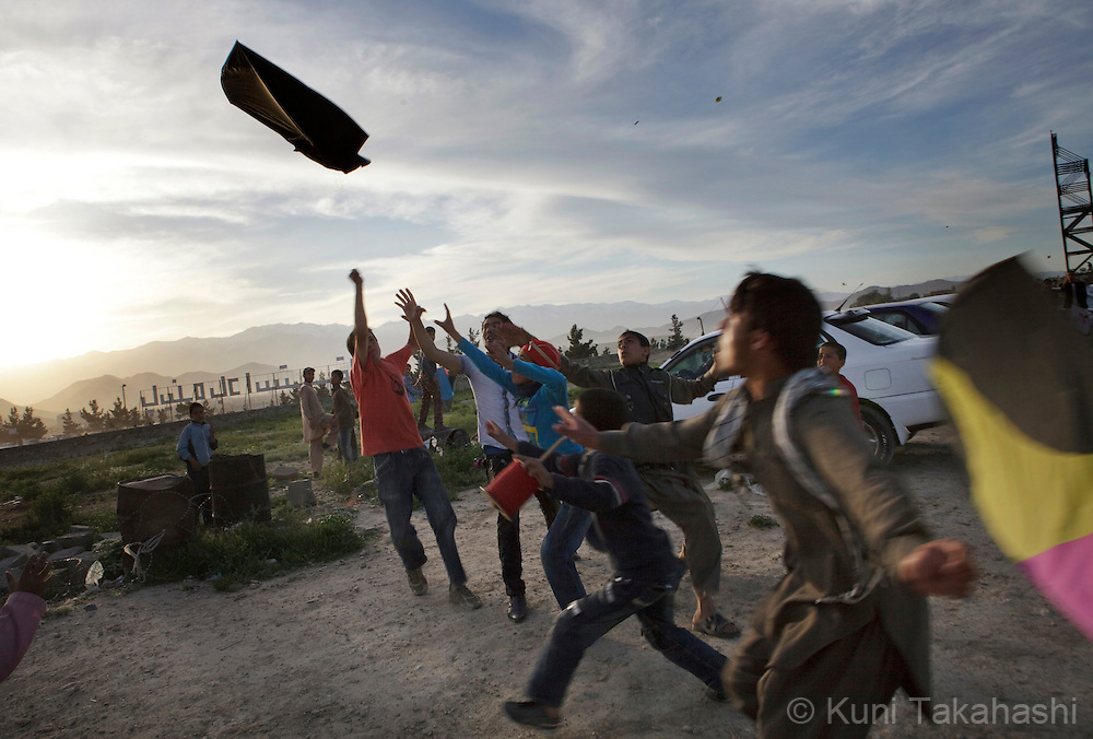 (Kabul Afghanistan - May 4, 2012).Boys reach to a falling kite of the hill in Kabul, Afghanistan on May 4, 2012. After years of war, severe poverty and poor security, Afghanistan is considered to be among the most dangerous places for children..(Photo by Kuni Takahashi)
