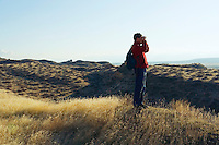 A man looking through binoculars on the hills above the Columbia River near Hanford Reach in Washington State...The only free flowing part of the Columbia left in Washington State...Model Release; 20070127_MR_A