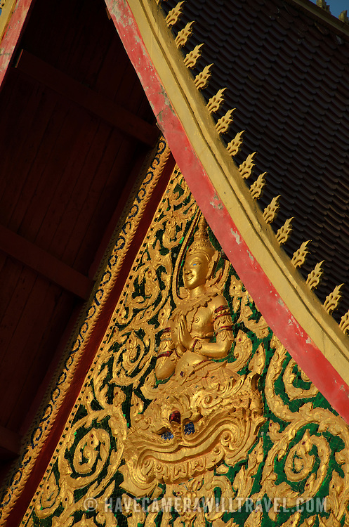 An ornately decorated roof of a Wat (Buddhist temple) in Vientiane, Laos. In the center of the decoration is a depiction of Buddha.