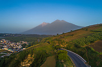 Aerial view of volcanos Fuego (left peak) and Acatenango (two right peaks)  in western Guatemala at sunrise on Tuesday, July 25, 2018. On June 3, Fuego experienced a large eruption that ended in many deaths, missing persons and property destruction in nearby towns like El Rodeo and Los Lotes. In this drone image, parts of Ciudad Vieja are seen.