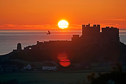 © Licensed to London News Pictures. 12/03/2012. Bamburgh, UK. Sunrise over the North Sea behind medieval Bamburgh Castle in Northumberland, UK on March 12th, 2012. Photo credit : Ben Cawthra/LNP