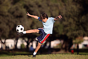 Young boy kicking a soccer ball in the park - authentic action - with copy space