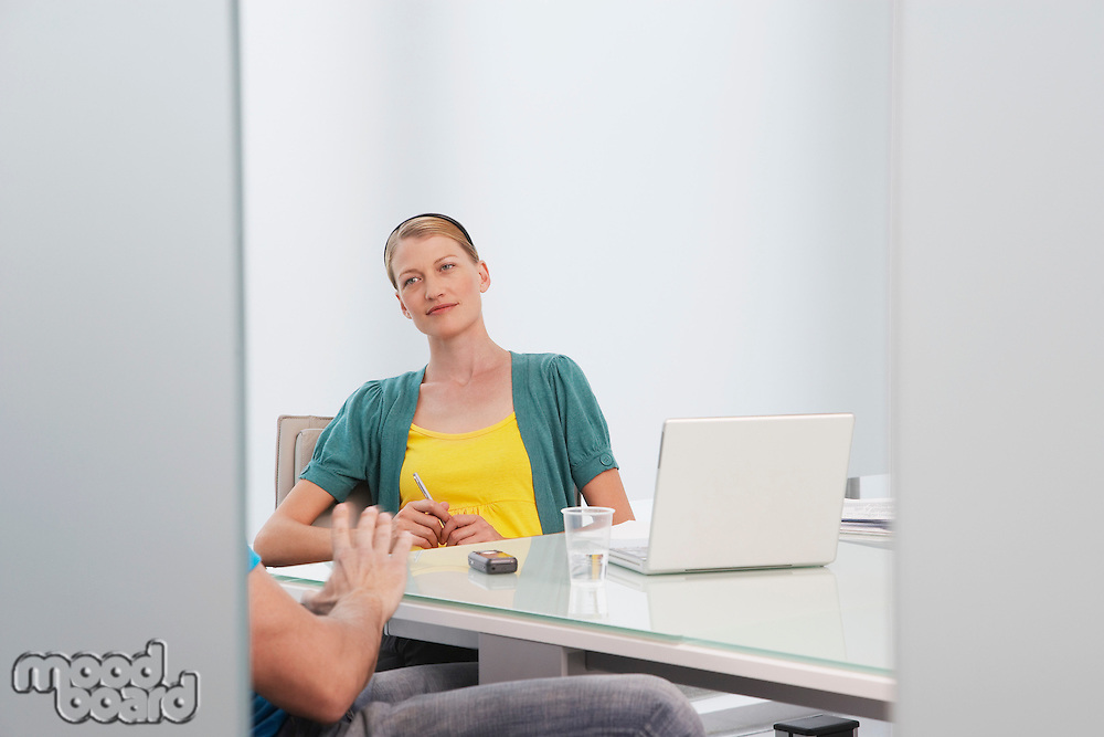 Woman talking to man (mid section) in office