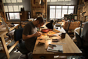 Ryan Hamonds uses a small hand plane to create violin parts at the North Bennett Street School, Boston.