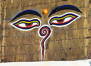 "Buddha Eyes gaze from one side of Swayambhunath, the ""Monkey Temple"" in Kathmandu, Nepal, Asia. On most every stupa (Buddhist shrine) in Nepal, giant Buddha Eyes (or Wisdom Eyes) stare from four sides of the upper cube. These four directions symbolize the omniscience (all-seeing) of a Buddha. The third eye (above and between the other two eyes) also symbolizes the all-seeing wisdom of the Buddha. The curled symbol (shaped like a question mark) in place of a nose is the Nepali character for the number 1, which symbolizes unity of all things."