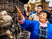 11 MARCH 2017 - KATHMANDU, NEPAL:  A Nepali Buddhist spins prayer wheels (dharma wheels) at Swayambhu Stupa. The second most important Buddhist stupa in Kathmandu, Swayambhu Stupa is also a historic landmark and has panoramic views of Kathmandu. It is sacred to both Buddhists and Hindus. The stupa is being rebuilt because it was badly damaged in the 2015 earthquake.   PHOTO BY JACK KURTZ