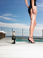Woman in bathing suit standing with champagne at outdoor pool low section