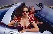 """A beautiful young woman in a red and white polka dot dress rides in a classic silver sports car. -- To determine pricing and license this image simply click """"Add To Cart"""" below --"""