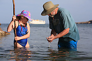 Marine biologist Bruce Mate shows young girl seastar as they wade in Sea of Cortez at Puerto Gato; Baja, Mexico.