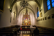 A man sits quietly in silent adoration at a catholic church in Krakow, Poland