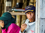 20 FEBRUARY 2019 - BAN LAEM, PHETCHABURI, THAILAND: A salt worker smokes a handrolled cigarette before starting work on one of the first days of the 2019 salt harvest in Ban Laem, Thailand. Ban Laem's salt fields are expanding because salt harvesters in Samut Sakhon and Samut Songkhram,  which are closer to Bangkok, are moving to Ban Laem as their land is turned into industrial parks.    PHOTO BY JACK KURTZ