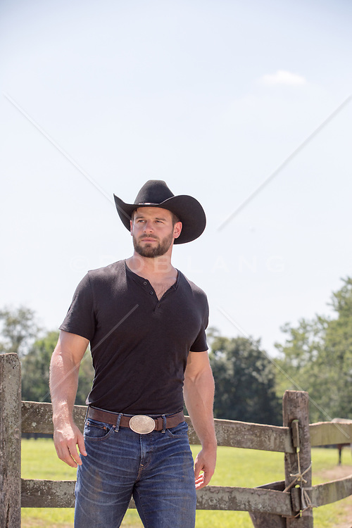 rugged cowboy by a spilt rail fence on a ranch