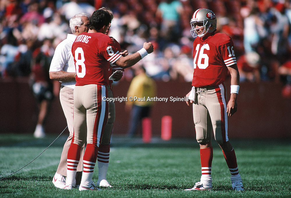 San Francisco 49ers head coach Bill Walsh, San Francisco 49ers quarterback Steve Young (8), and San Francisco 49ers quarterback Joe Montana (16) talk during pregame warmups at the NFL football game against the Atlanta Falcons on Sept. 18, 1988 in Anaheim, Calif. The Falcons won the game 34-17. (©Paul Anthony Spinelli)