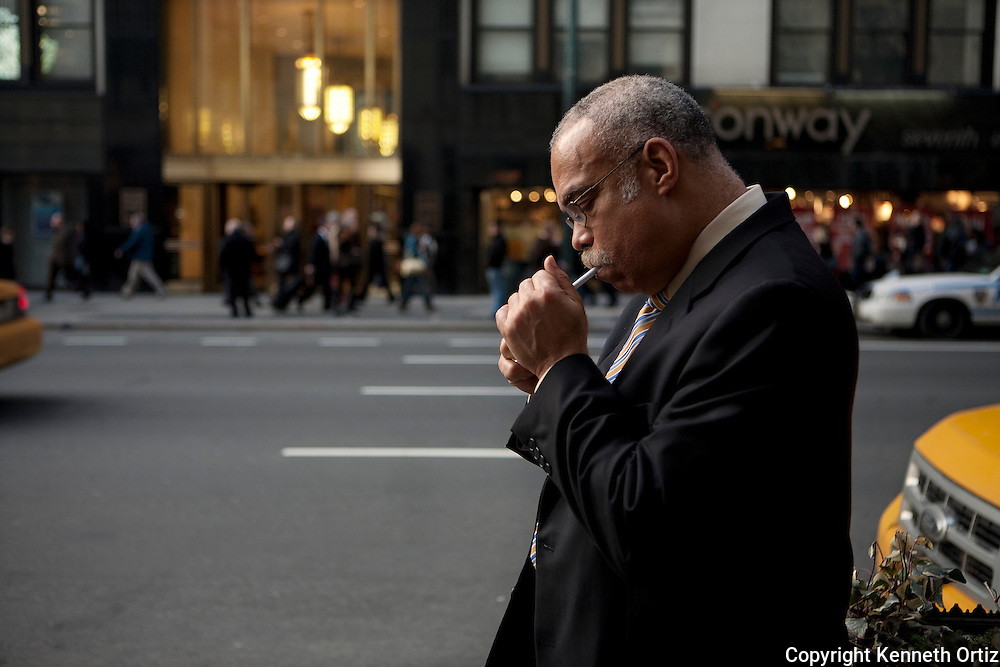 A man on 7th Avenue in New York City takes a moment to light up his cigarette.