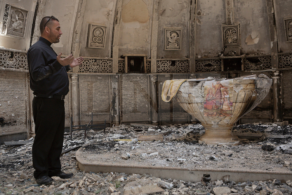 © Licensed to London News Pictures. 04/11/2016. Hamdaniyah, Iraq. Father Ignatius Offy, a Christian priest, prays at the fire damaged alter in the burnt out shell of the Syriac Catholic Church of Mar Behnam and his sister Mart Sarah in the recently liberated Christian town of Hamdaniyah, Iraq. The church was vandalised and burnt by Islamic State militants during their two year occupation of the town which was retaken by Iraqi Security Forces during the ongoing Mosul Offensive.<br /> <br /> Although located close to a front line, littered with improvised explosive devices and pieces of unexploded ordnance the Christian town of Hamdaniyah has only recently been cleared of ISIS extremists who stayed behind to fight. After the town's liberation as part of the Mosul Offensive residents and priests of the town are now free to take short trips to assess damage, salvage possessions and clear up the mess left by militants during their two year occupation.<br /> <br /> Hamdaniyah, and much of the Nineveh plains, were captured by the Islamic State during a large offensive on the 7th of August 2014 that saw the extremists advance to within 20km of the Iraqi Kurdish capital Erbil. Residents of the town, who included many Christian refugees who escaped there after the fall of Mosul, were then forced to seek sanctuary in the Kurdish areas. In the year and two months of the ISIS occupation churches were burnt, homes were put into use as militant accommodation and bomb factories and some buildings destroyed by coalition airstrikes. Photo credit: Matt Cetti-Roberts/LNP