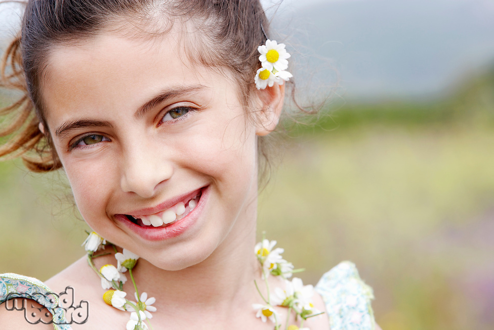 Smiling Pre-teen wearing necklace of flowers and flower behind ear close-up