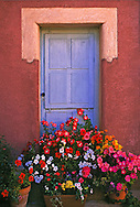 Doorway and flowers, Roussillon de Provence also known as the Ochre City, France...Doorway and flowers, Roussillon de Provence also known as the Ochre City, France.