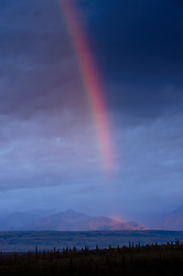 A late evening rainbow appears before a completely cloud shrouded Mt. McKinley in Denali National Park and Preserve in Alaska. The view is from the Wonder Lake campground. The visible mountains are the foothills of the Alaska Range.