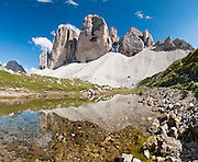 "A pond reflects Tre Cime di Lavaredo (Italian for ""Three Peaks of Lavaredo,"" also called Drei Zinnen or ""Three Merlons"" in German), which are distinctive icons of the Alps, in the Sexten Dolomites of northeastern Italy, Europe. Until 1919 the peaks formed part of the border between Italy and Austria. Now they lie on the border between the Italian provinces of South Tyrol and Belluno and still are a part of the linguistic boundary between German-speaking and Italian-speaking majorities. Cima Grande rises to 2999 meters (9839 feet), between Cima Piccola  2857 m (9373 ft) and Cima Ovest  or ""Western Peak"" 2973 m (9754 ft). The Dolomites were declared a natural World Heritage Site (2009) by UNESCO. Panorama stitched from 9 overlapping photos."